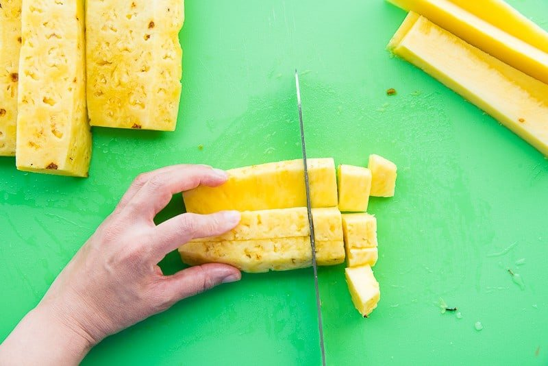 A hand holds sections of pineapple while a knife cuts them into chunks