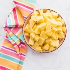 A portrait image of a pink bowl filled with cut pineapples. A multi-colored kitchen towel sits next to the bowl
