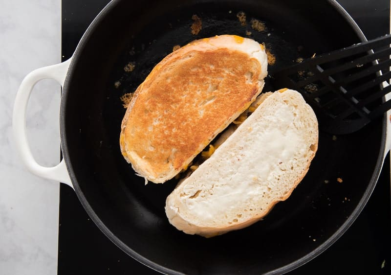 One sandwich is flipped over in a pan while the other is showing it's buttered top.
