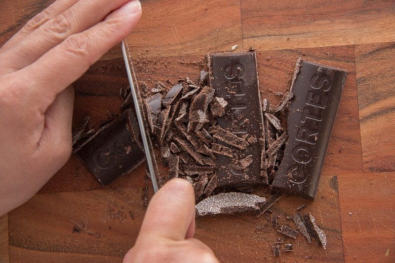 A hand holding a knife is chopping the sweet chocolate into chunks