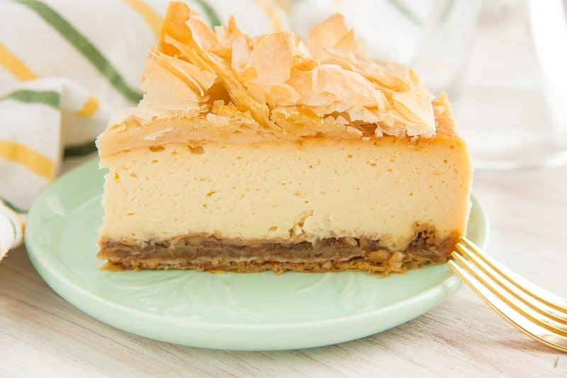 A slice of cheesecake sits on a mint green plate a gold fork's tines peek out on the right