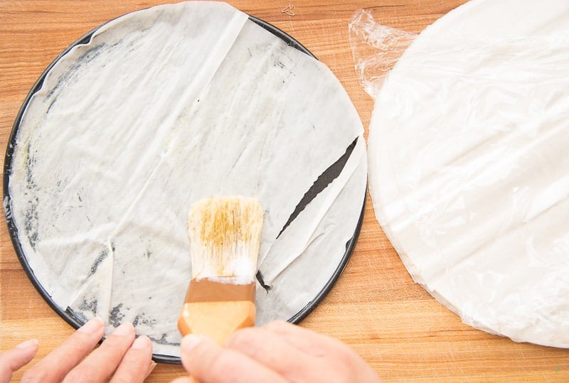 Brushing melted butter between each layer of phyllo dough