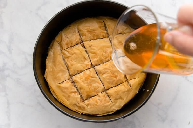 Pour half of the baklava syrup onto the hot baklava crust