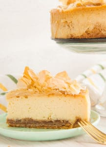 A sideview of a slice of Sense & Edibility's Honey Cheesecake with Baklava Crust sitting on a green plate