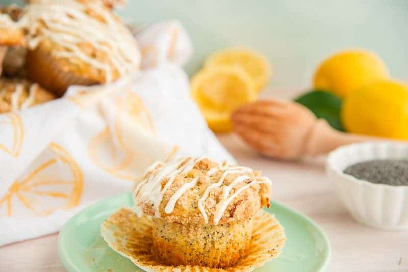 A lemon poppy seed muffin is on a mint green plate. The muffin wrapper is slightly pulled away from the muffin