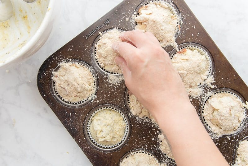 A hand sprinkles almond streusel over the scooped lemon poppy seed muffin batter