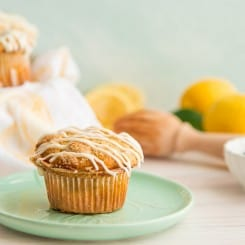 A landscape image of a single Lemon Poppy Seed Muffin on a mint green plate.