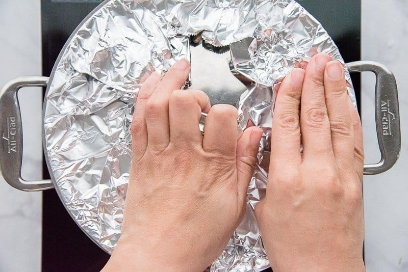 Seal the pot by pressing a piece of aluminum foil beneath the lid