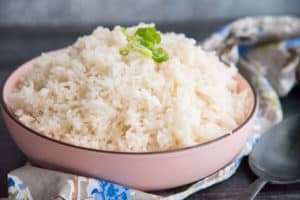 A side view image of a pink bowl filled with Steamed White Rice.