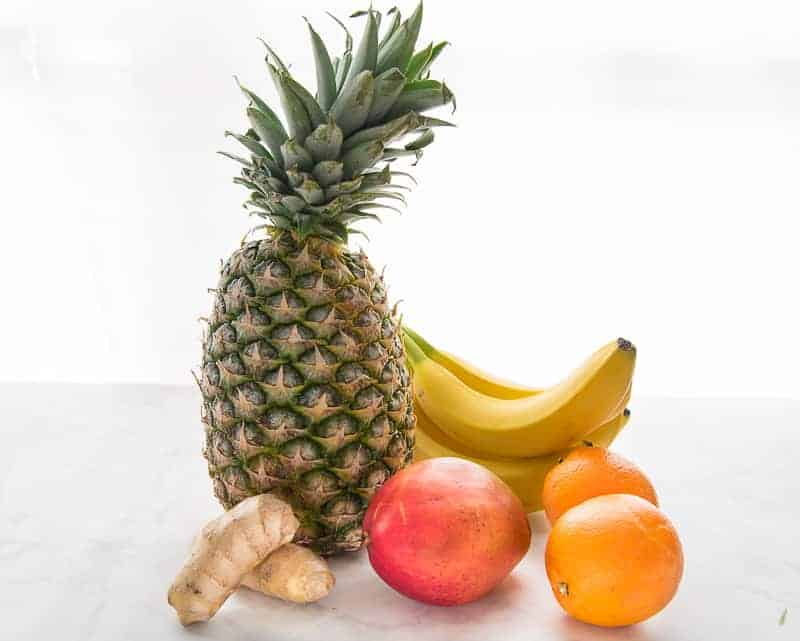 The ingredients for a vitamin C bomb smoothie: a pineapple, bananas, mango, oranges, and ginger