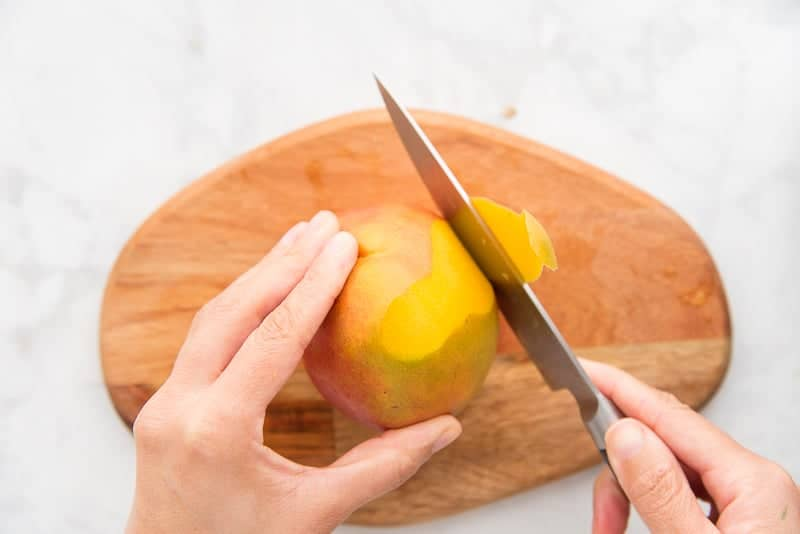 A hand holds a knife that's slicing away the peel of a mango on a wooden cutting board