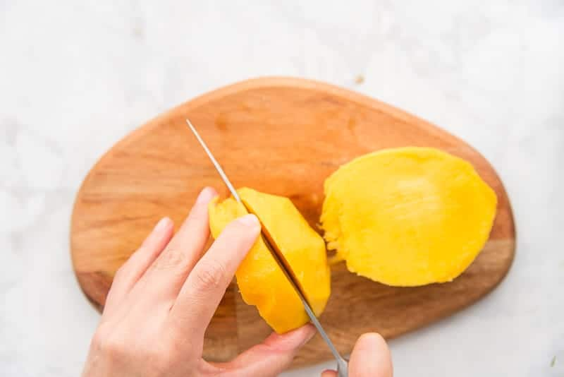a hand holding a knife slice the flesh from the pit of the mango on a wooden cutting board