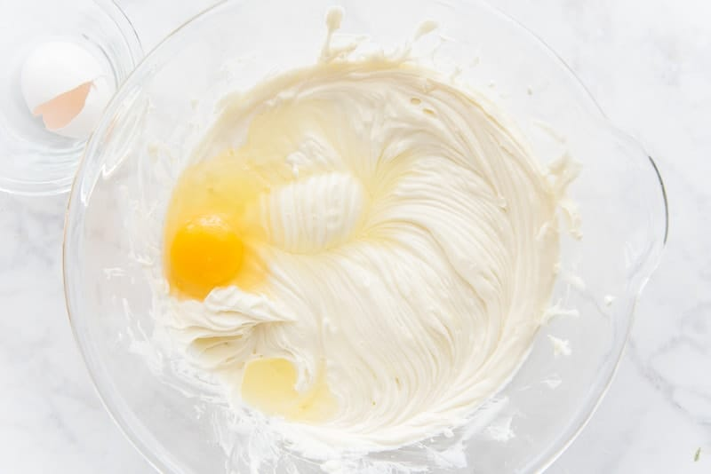 The eggs are being added to the batter one at a time