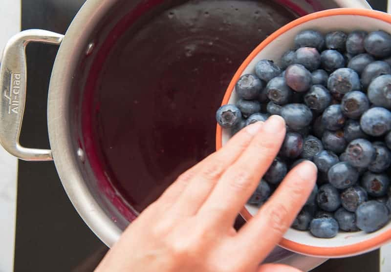 A hand adds blueberries to the blueberry glaze