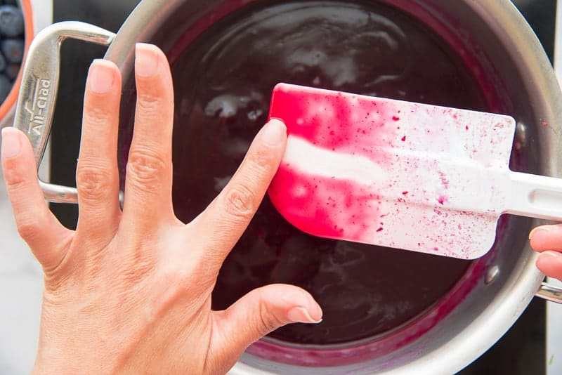 A finger is used to check the consistency of the blueberry glaze on a white spatula
