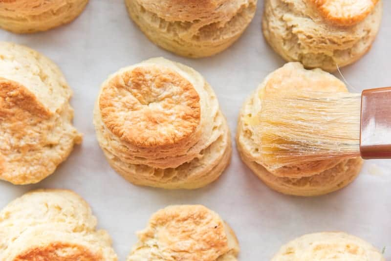 A pastry brush brushes melted butter onto the tops of the baked Buttermilk Biscuits