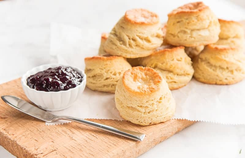 A stack of buttermilk biscuits on a wooden board with white paper next to a bowl of jam