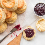An overhead image of a stack of buttermilk biscuits and jam on a wooden board