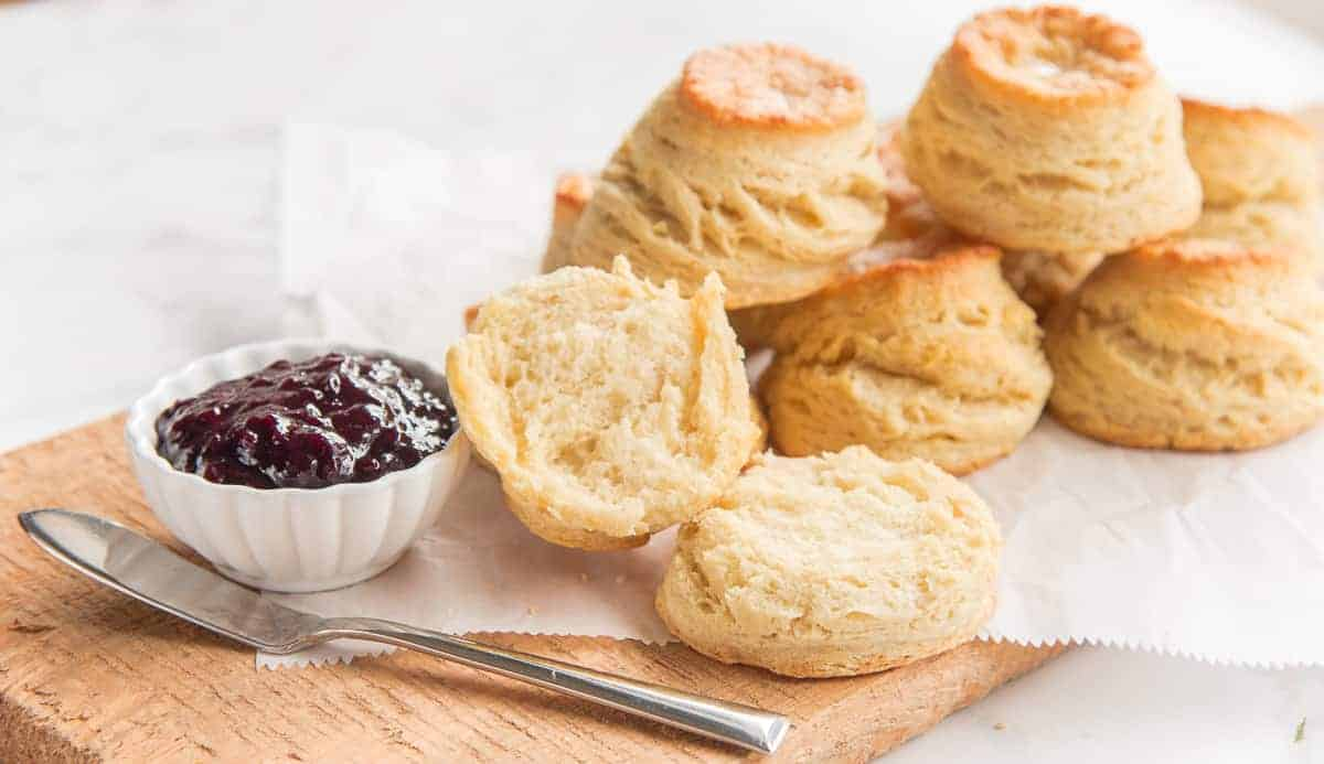 A stack of Buttermilk Biscuits, blackberry jam and a knife sit on a wooden board