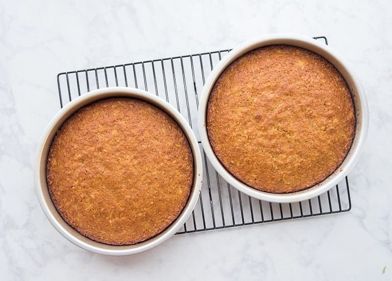 The baked cakes sit on a cooling rack in their silver pans