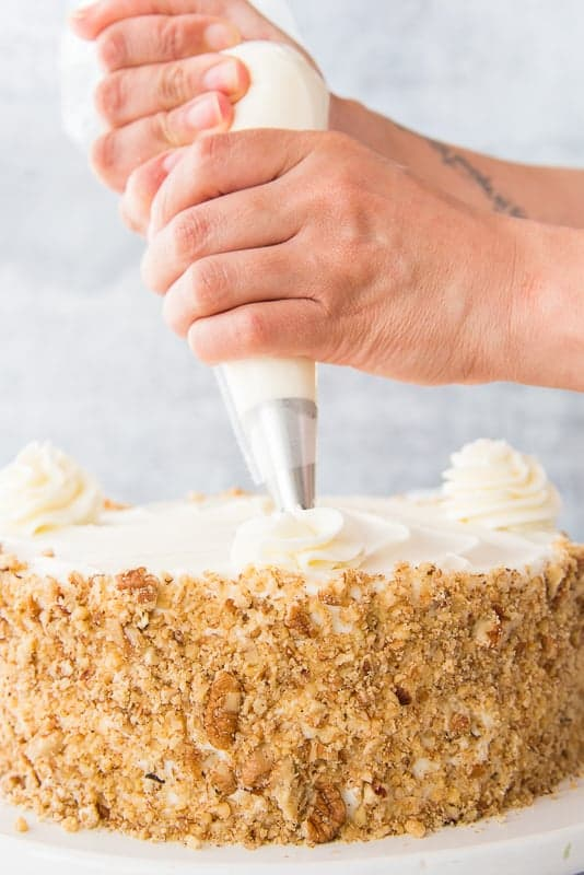 A hand holds a piping bag to pipe rosettes onto a loaded carrot cake