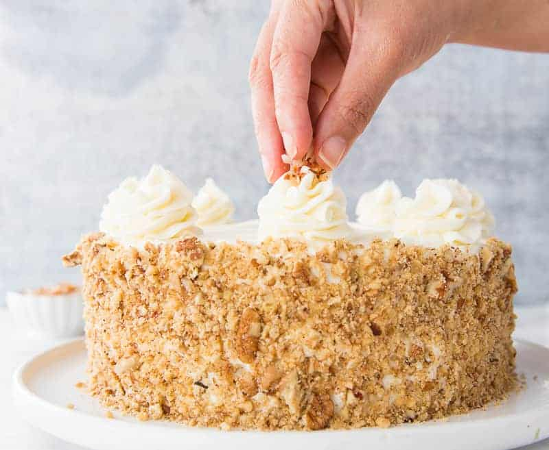 A hand sprinkles nuts and coconut on top of a rosette on a whole loaded carrot cake.