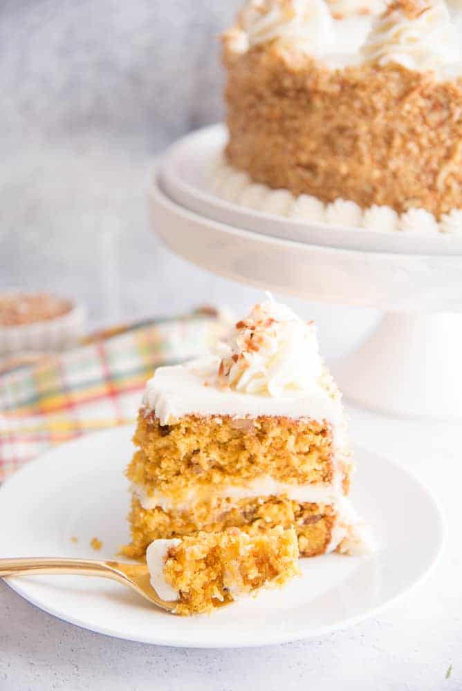 A side view of a bite of carrot cake on a gold fork