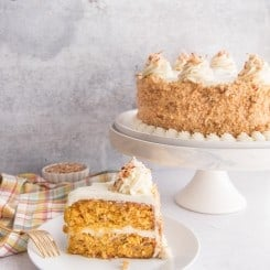 A slice of carrot cake sits on a white plate