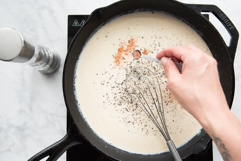 A hand uses a measuring spoon to sprinkle spices into the pan gravy