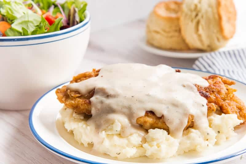 Chicken Fried Chicken covered in Pan Gravy sits on a bed of mashed potatoes. A salad and plate of biscuits is in the background