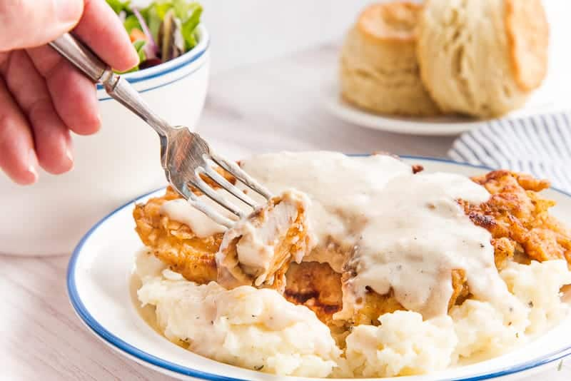 A fork picks up a piece of the Chicken Fried Chicken with Pan Gravy