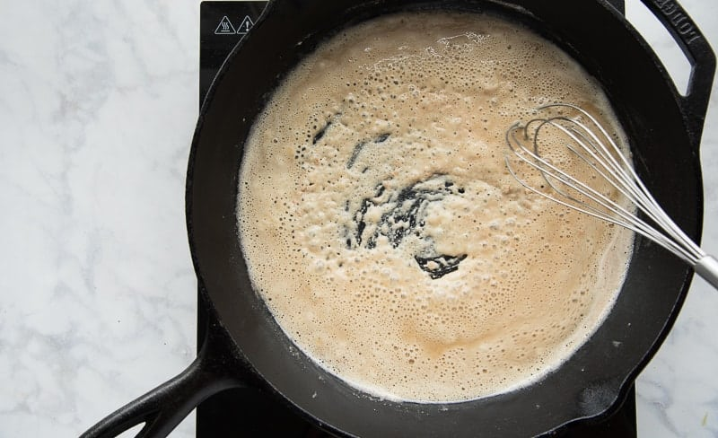 A whisk stirring a brown roux in a black cast iron skillet