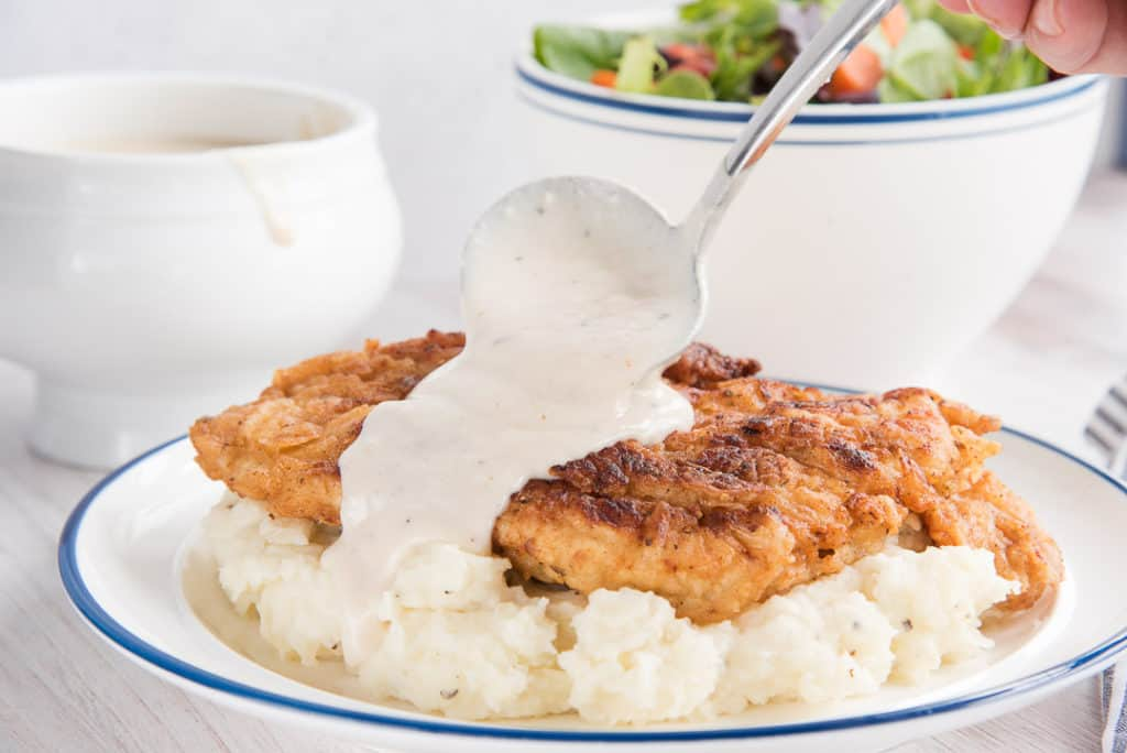 A hand ladles pan gravy over fried chicken and mashed potatoes