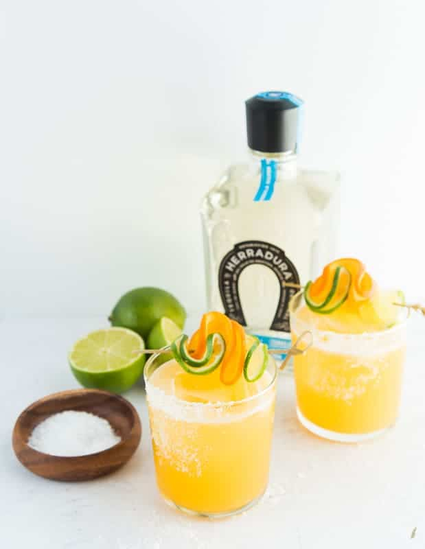 A portrait image of two Chispas Margaritas with a bottle of tequila in the background