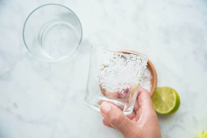 A glass that has been rimmed with sea salt is held by a hand