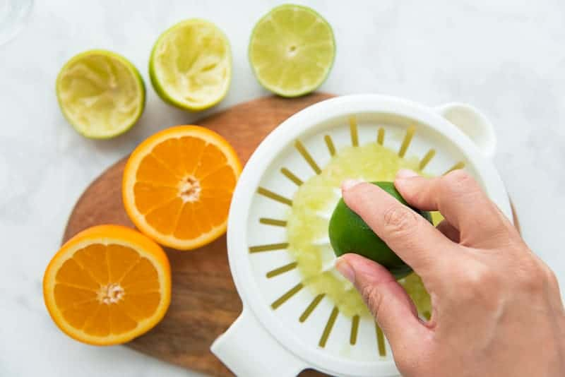 Limes and an orange are juiced to add to the Chispa Margaritas mix