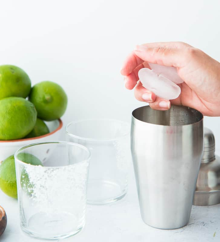 Ice cubes are being dropped into a cocktail shaker