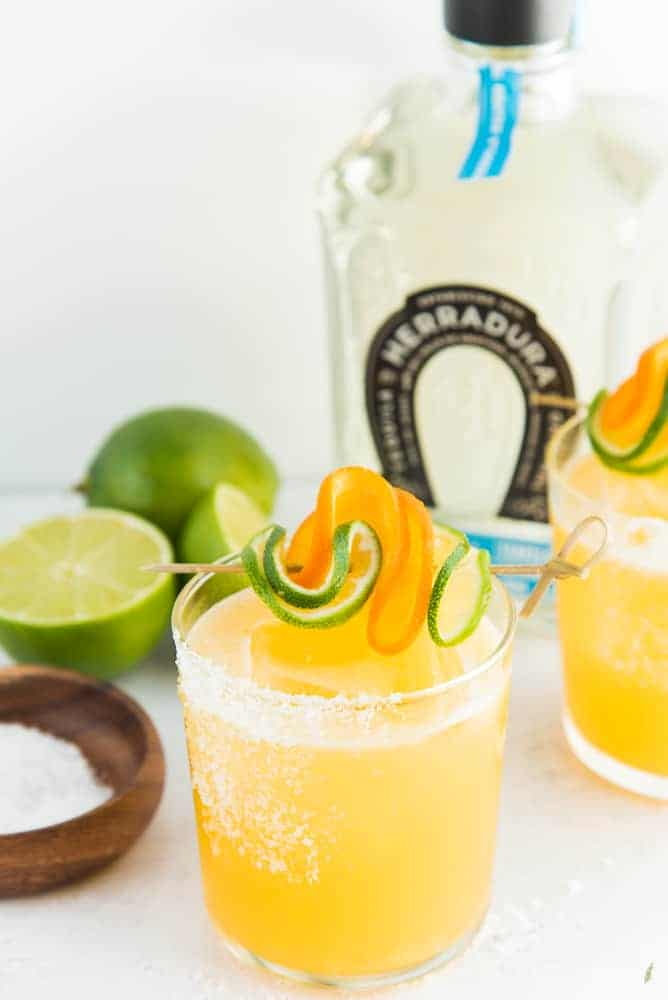 A portrait image of a Chispa Margaritas. A bowl of salt and limes is on the left, a bottle of tequila is to the right