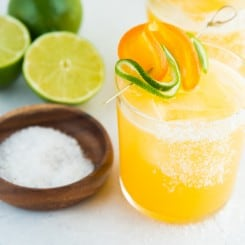 An up close image of a salt-rimmed glass filled with Chispa Margarita. A bowl of salt sits next to the cocktail