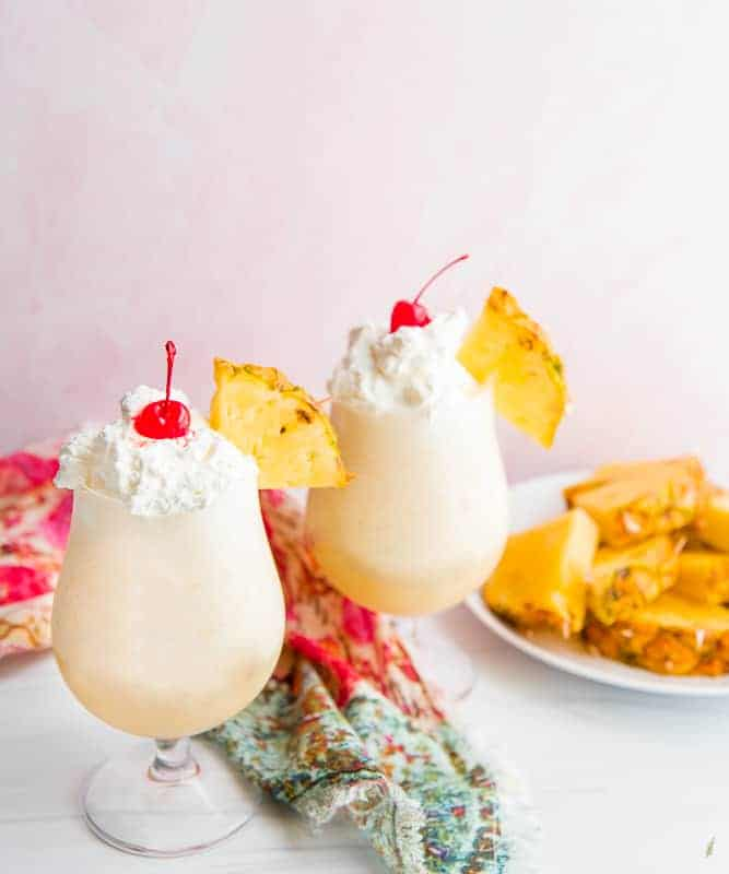 A portrait image of two Piña Coladas topped with whipped cream and a cherry