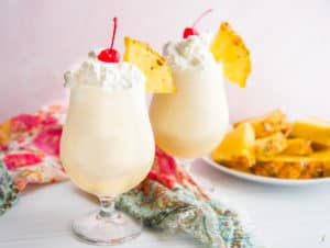 Two glasses filled with Classic Piña Colada cocktail and topped with whipped cream and a cherry