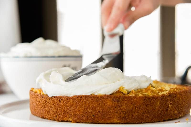 A spatula spreads the Cream Cheese Frosting over a layer of cake