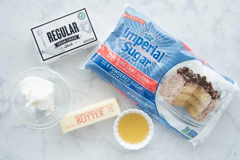 The ingredients needed for Cream Cheese Frosting on a marble countertop