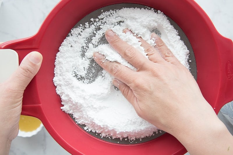 A hand uses a red sifter to sift the powdered sugar