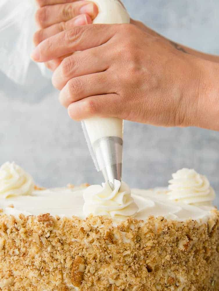 A hand pipes a icing rosette onto a cake