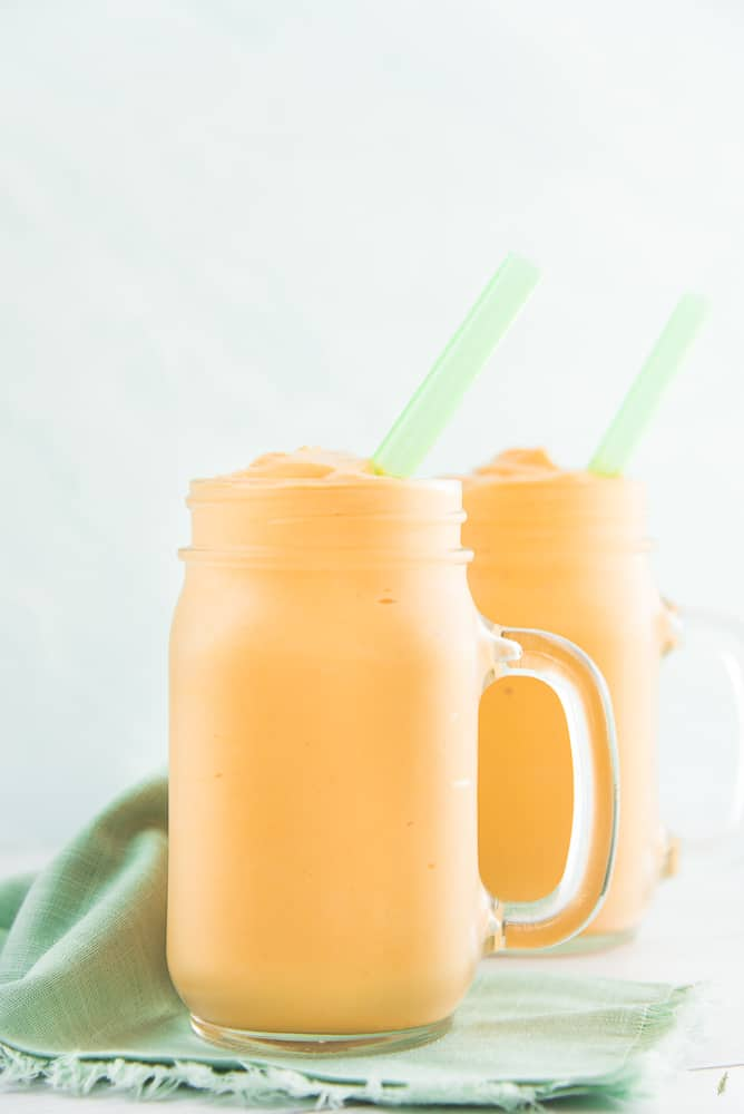 A portrait image of two glass jars filled with Sense & Edibility's 4 Ingredient Fruit and Yogurt Smoothie a green straw is in the smoothie and a green napkin sits next to them