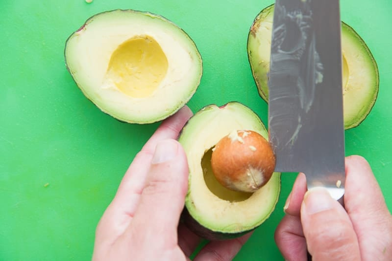 The heel of a knife is used to remove the avocado pits