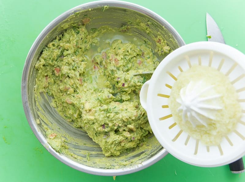 Lime juice is poured into a mixing bowl filled with guacamole
