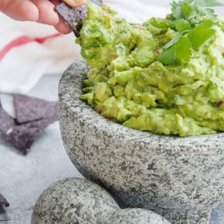 A hand uses a blue corn tortilla chip to scoop some guacamole