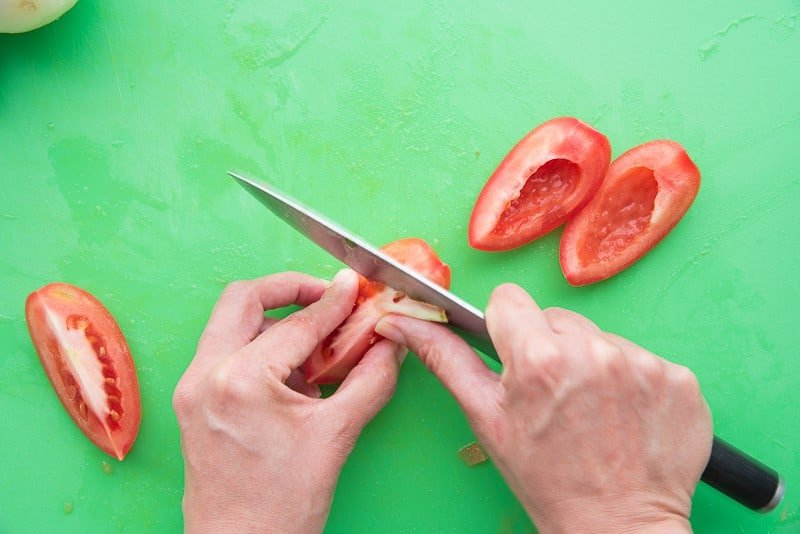 A knife is used to remove a tomato's membrane and seeds